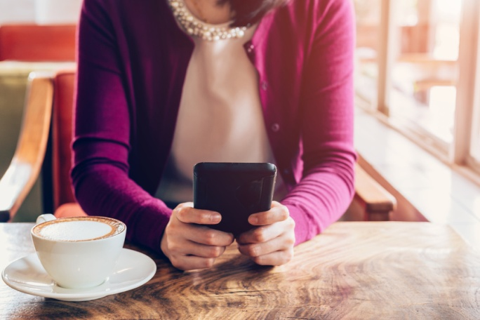 Woman using mobile phone in cafe. Female sitting in cafe and cup